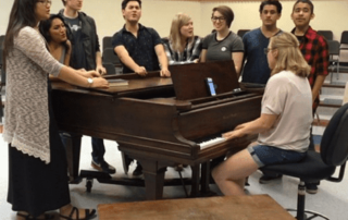 students sing while standing around piano in class room