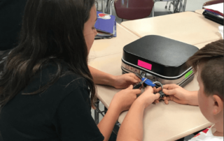 Students work together to solve a breakout box