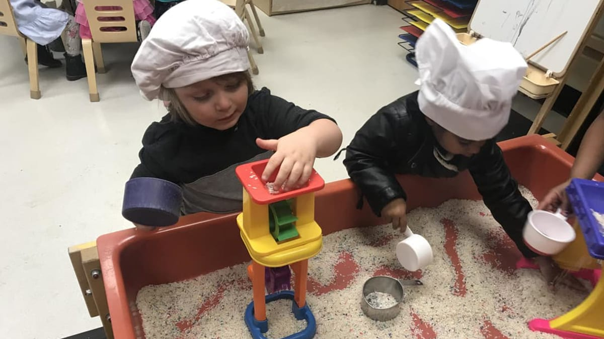 2 preschool students play in the sand