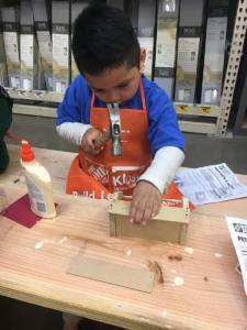 Preschool boy hammering nails at Home Depot