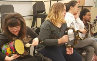 Students play drum and tambourines in the DLC Music Classroom at Straub