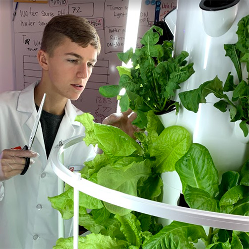 Student in Agriscience lab with scissors
