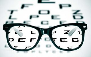 Glasses resting on top of an eye chart