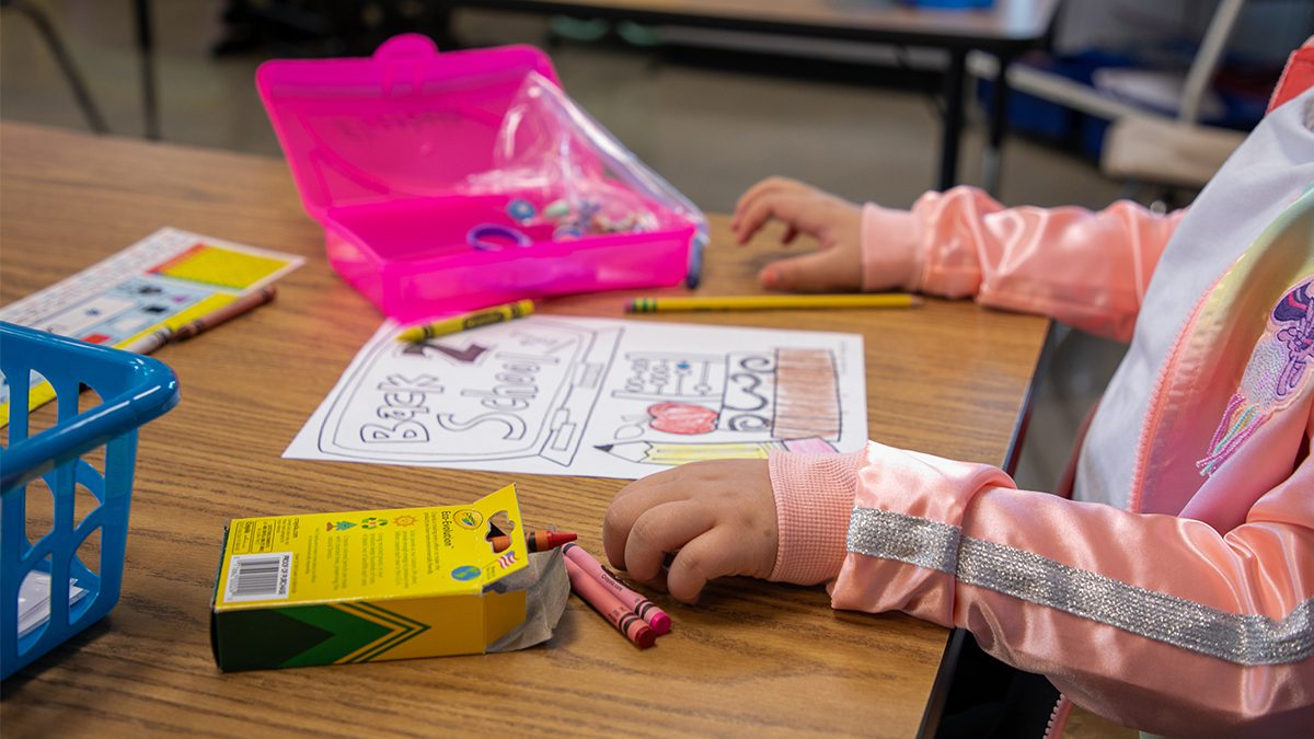 Student drawing picture with Crayons