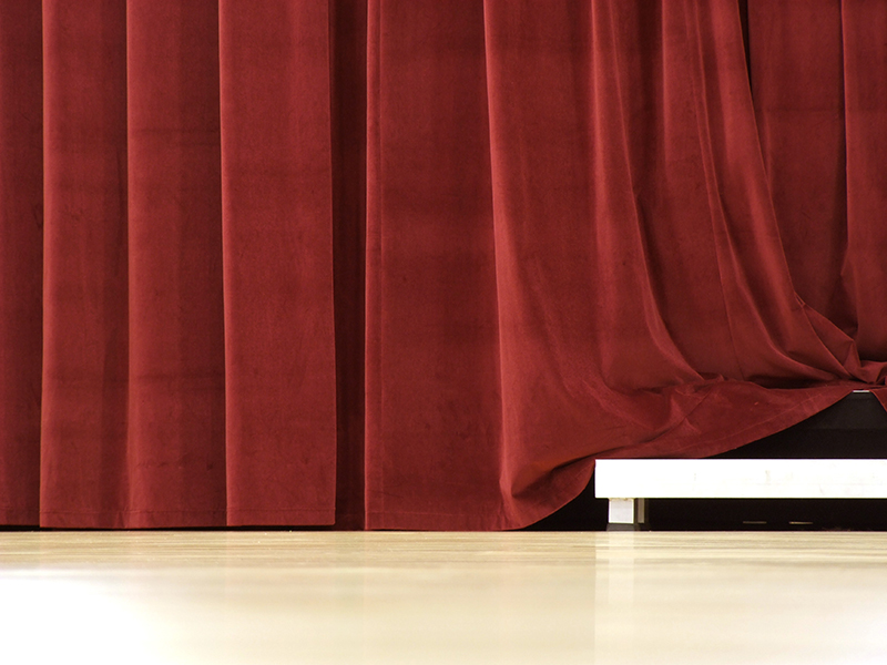 red stage curtain with stand peaking through