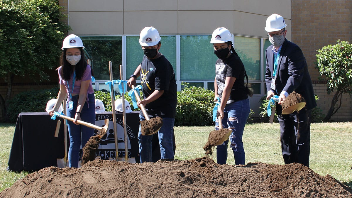 Stephens Middle School students and staff turn over dirt with shovels at groundbreaking ceremony